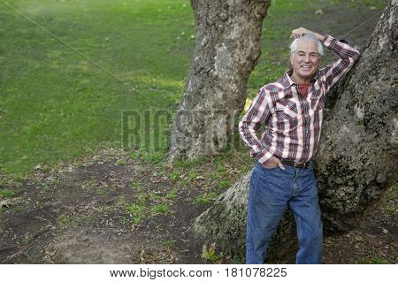 Senior Hispanic man leaning against tree