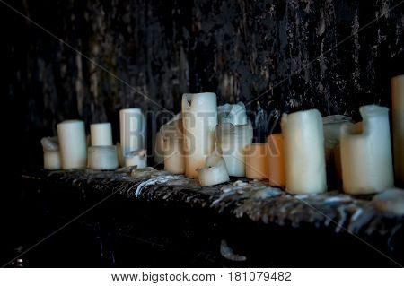 Candle stand on a dark surface against a dark wall, all in soggy wax. A lot of candles, the fire is lit. Extinguished candles