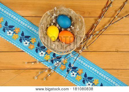 Композиция из яиц в плетеной корзине и веточек вербы с ярким орнаментом на дереве