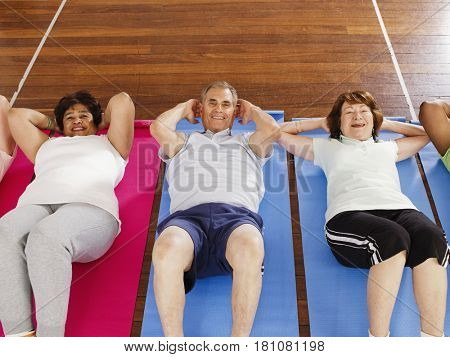 Multi-ethnic adults doing sit-ups in exercise class