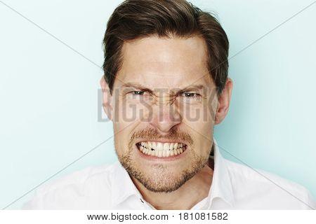 Angry man clenching teeth at camera studio shot