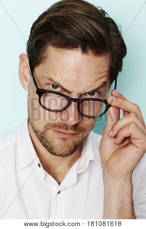 Portrait of quizzical man in eyeglasses studio shot
