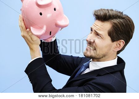 Nervous businessman shaking piggy bank daylight portrait