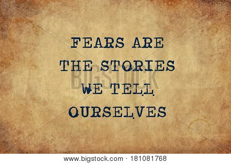 Inspiring motivation quote of fears are the stories we tell ourselves with typewriter text. Distressed Old Paper with Typing image.