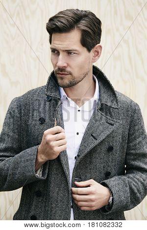 Posing man in grey coat looking away