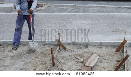 Relax Time Of Worker Working Digs A Hole With A Shvel And Spade In The Sand At Road Construction Sit
