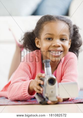 Mixed race girl holding video camera