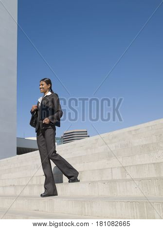Indian businesswoman descending stairs outdoors