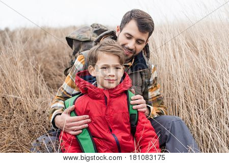 Father With Son Sitting In Grass