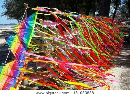 display rack of kites for sale at the beach, mass of kite tails fluttering in the wind, Songkhla, Thailand