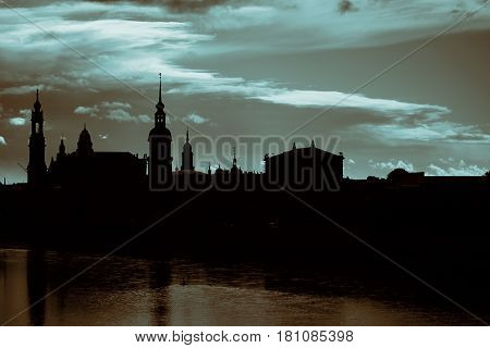 Dark silhouettes of the towers of the old city in Dresden against the backdrop of dramatic sky