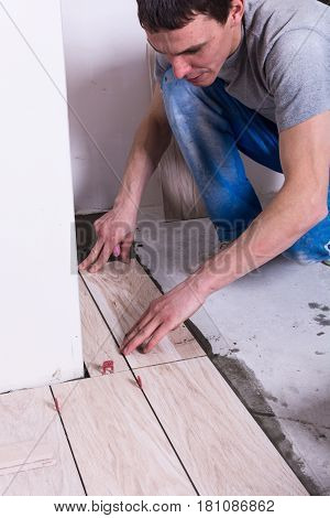Tiler installing ceramic tiles on a floor