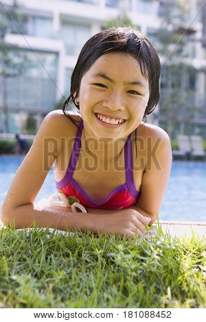 Asian girl getting out of swimming pool