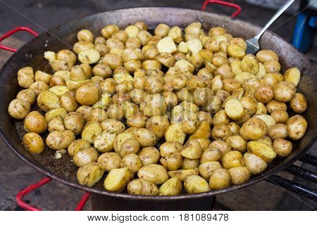 Country fair cooking. Roasted potatoes cooked outdoors in big metal cauldron pot. Cookout vegetable meals. Fresh organic, healthy snack cooked on grill flame. Street fast food.