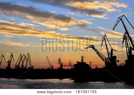 Harbor against red sunset background in summer