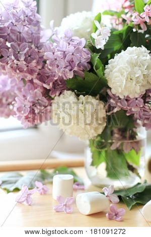 Bouquet of fresh lilac flowers in transparent glass vase on the table at window in spring summer morning. Vertical floral background. Soft focus. Pastel colored.
