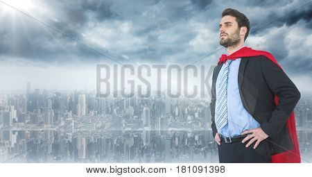 Digital composite of Business man superhero with hands on hips against skyline and flare