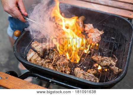 Grill steaks on metal grate with flame. Chef hands cooking roasted meat barbecue with lots of fire. BBQ fresh beef chop slices. Traditional dish on charcoal, street food