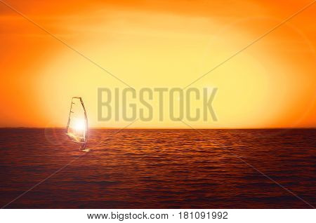 Windsurfer silhouette at sea sunset. Beautiful beach seascape. Summertime watersports activities vacation and travel concept background