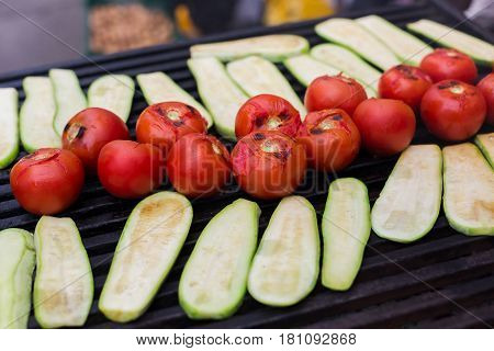 Vegetable barbecue roasted on metal grill grate. Diet vegan bbq. Zucchini and tomatoes closeup at picnic outdoors