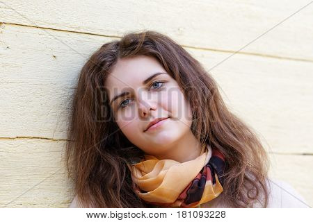 Girl with a secret smile on the background of a yellow wall