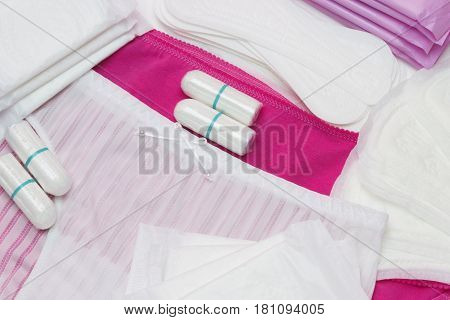 White and pink pants. Woman hygiene protection menstruation sanitary pads and cotton tampons. Protection for woman critical days gynecological menstruation cycle