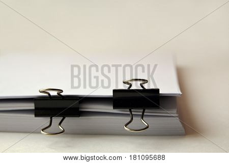 Stack of business report documents paper files with black clips background with copy space. pile of blank paper sheets with clips on it.