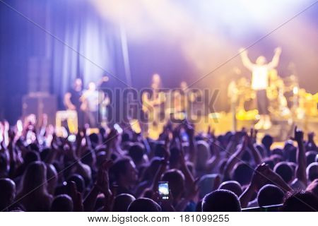 Crowd at concert and blurred stage lights . Close up of photographing with smartphone during a concert .