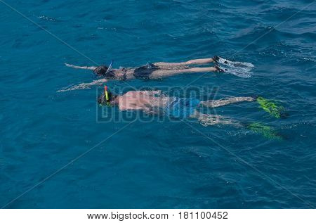 couple of swimmers man and pretty girl or woman with diving masks snorkels flippers snorkeling in transparent sea or ocean water surface on blue background. Idyllic summer vacation. Sport hobby