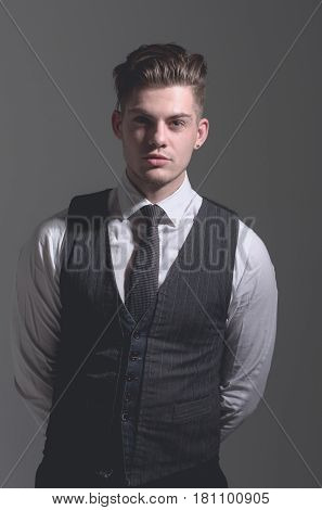 Handsome man or fashion model with stylish haircut hair in fashionable wear vest tie and white shirt posing on grey background