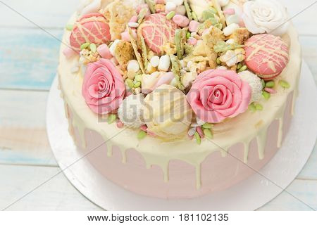 Pink cake with flowers and cupcakes on a white plate