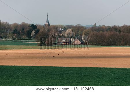 Old Dutch Village With Church In Hilly Landscape.