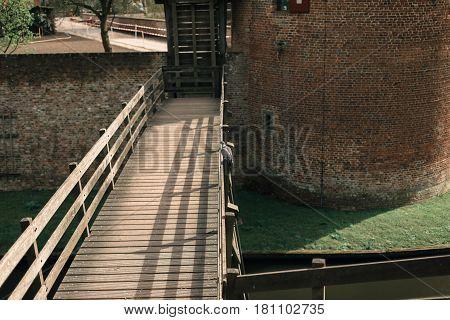 Dove Sitting On Wooden Bridge Railing Of Castle.