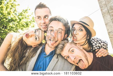 Group of best friends taking selfie outdoor with back lighting - Happy concept with young people having fun together - Cheer and friendship at city tour - Retro vintage filter with focus on middle guy