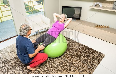 Active elderly couple training with swiss ball at home - Retired people at exercise fitness activity in gym living room - Mature man coaching lady woman on crunch sit ups abdominal sport execution