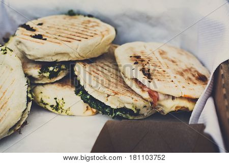 Street vendor selling pitas sandwiches outdoors. Mexican cuisine snacks closeup. Fast food commercial kitchen.