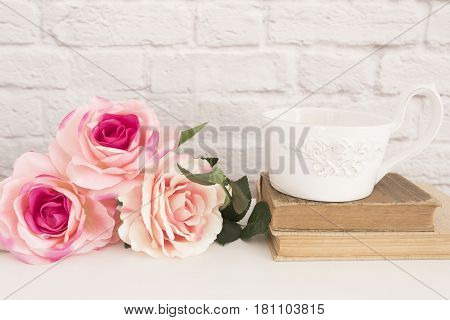 Bouquet Of Roses On A White Desk, A Large Cup Of Coffee Over Old Books, Romantic Floral Frame Backgr