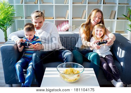 Happy family sitting on a sofa and playing video games