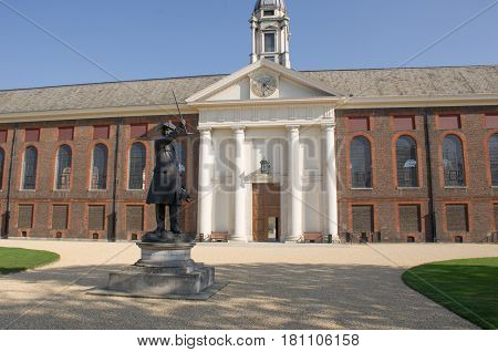 Frontage of Royal Chelsea Hospital with pensioner statue in foreground