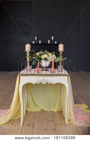 Vase with a bouquet of white and cream flowers stands on a table decorated with a cloth and candles against a dark wall. Focus on the vase vertical photo