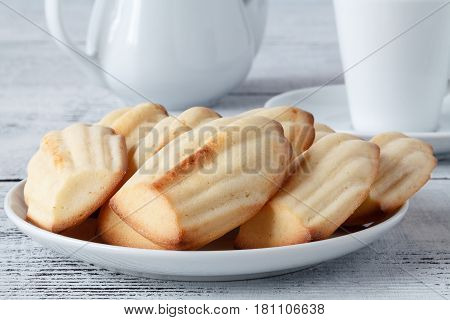 Delicious madeleines on white plate with coffee