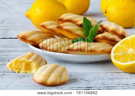 Freshly baked french madeleines with lemon on table