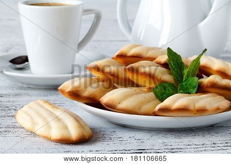 Sugar powdered madeleines cookies with mint and coffee
