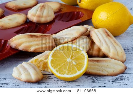 Madeleine cookies with lemon on white table