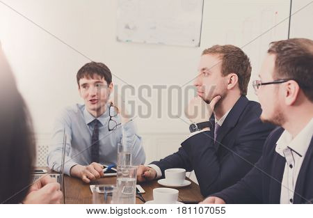 Business people meeting, analyzing sales. Young businessmen in modern office, team discussion at workplace. Brainstorming and communication with partners for startup.