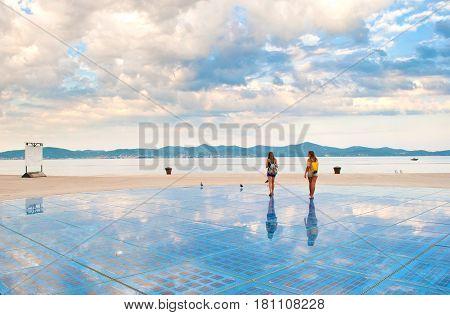 Two Girls Walking On Top Of Sun Salutation Installation