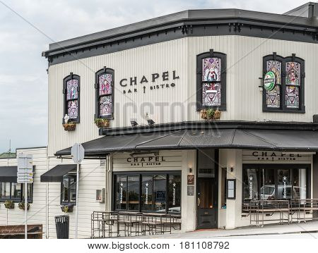Auckland New Zealand - March 1 2017: Heineken bar and bistro in Ponsonby Road is named Chapel and features stained glass windows with Christian religious themes. Gray sky white facade black trim.