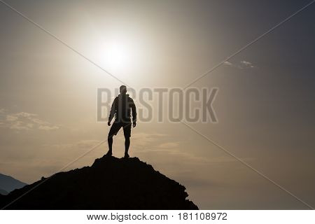 Man celebrating or praying in beautiful inspiring mountains sunrise. Hiker silhouette on mountain top hiking or climbing. Looking and enjoying inspirational sunshine landscape on rock Crete Greece.