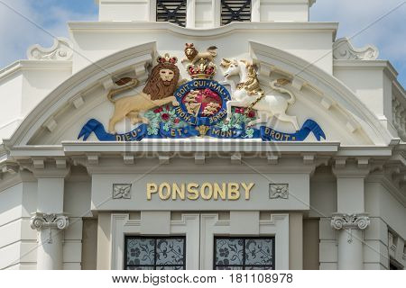 Auckland New Zealand - March 1 2017: The cream white mansion with clock tower at intersection of Ponsonby Road and College hill. Closeup of British Royal crest.