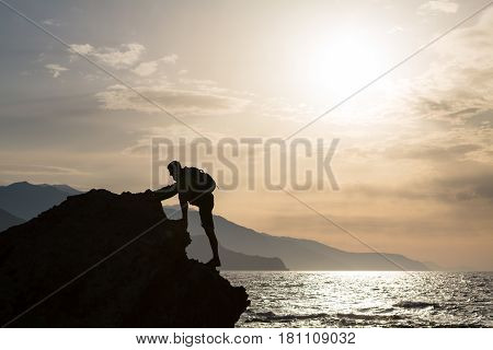 Climbing hiking silhouette in mountains and ocean rock climber in inspirational sea landscape and islands on mountain peak. Accomplished fit man on sunrise adventure and lifestyle concept.